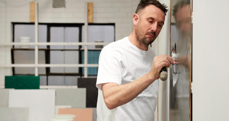 eddie bishop applying polished plaster to wall