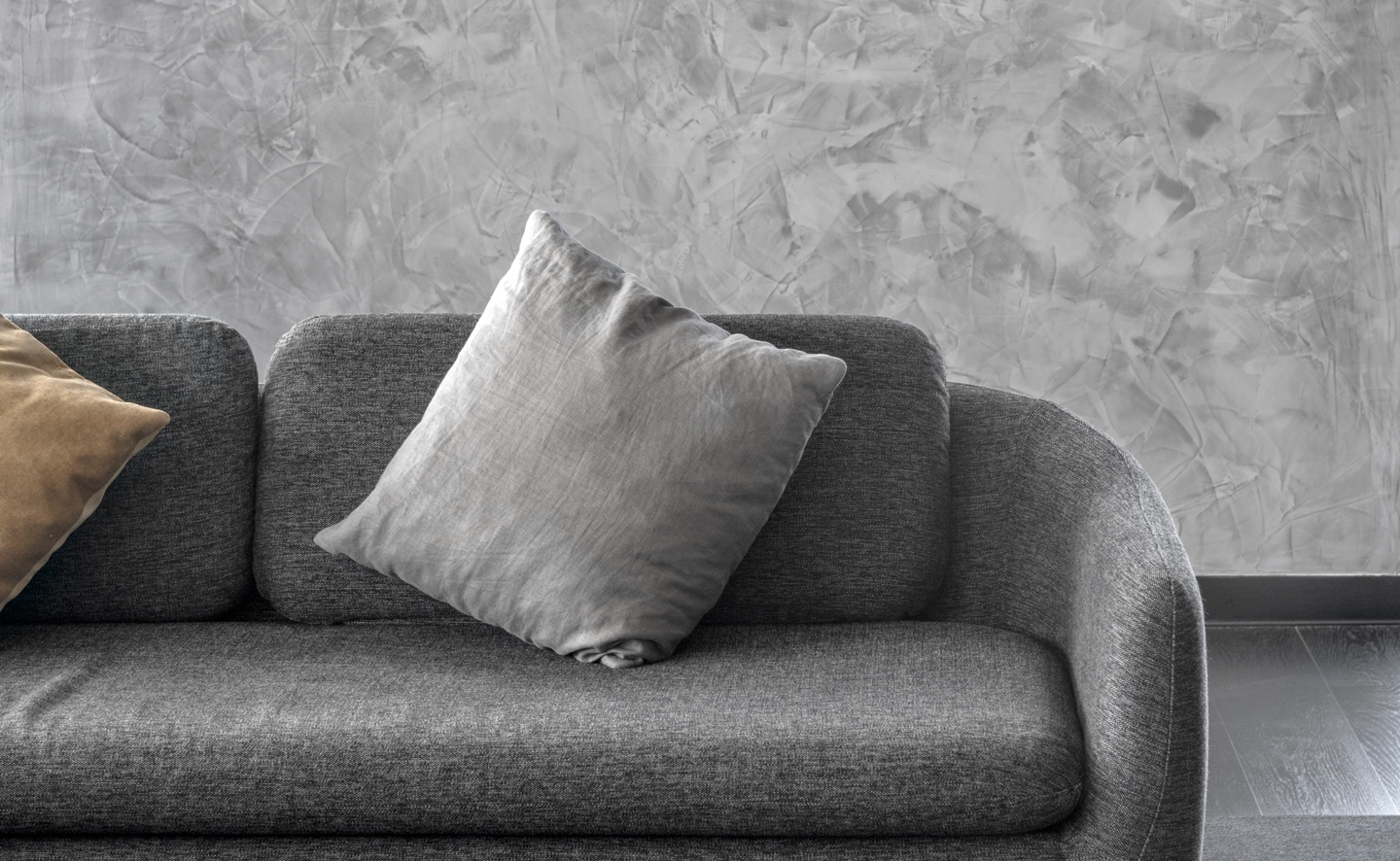 grey polished plaster behind a grey couch with cushions