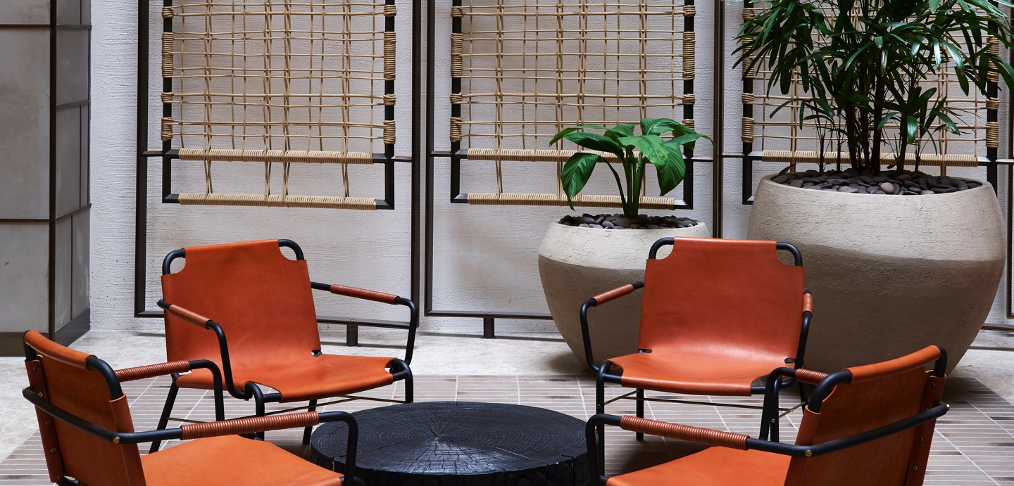 raked wall finish with rope detailing and orange leather chairs in the foyer at 161 collins st melbourne