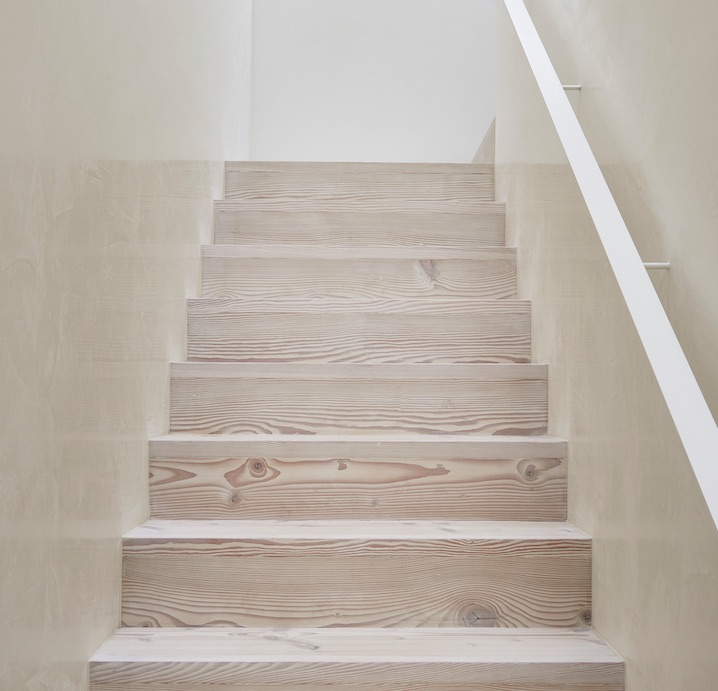 Waterstone polished plaster or venetian plaster wall finish in a light bright colour on this staircase in light wood tones.