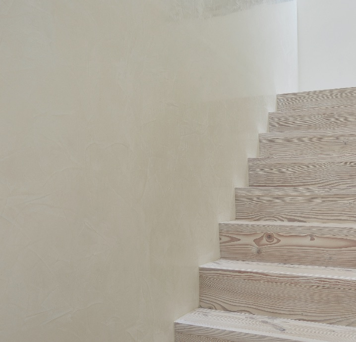 polished plaster venetian plaster wall finish on the staircase in a luxury private residence in armadale. Light polished plaster with wood stairs.