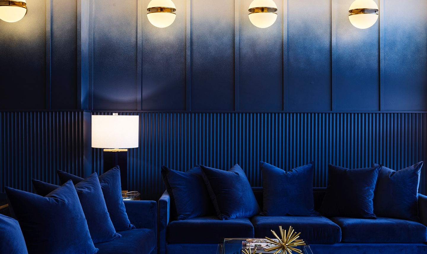 A wide shot of the le plonc blue ombre wall with blue couches and cushions. Designed by Greg Natale